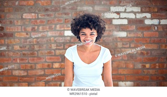Happy woman with curly hair against brick wall