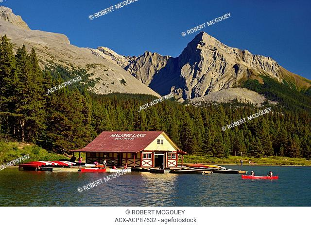 An image of Maligne Lake showing the boat house with people paddeling canoes in the rocky mountains in Jasper National Park Alberta Canada