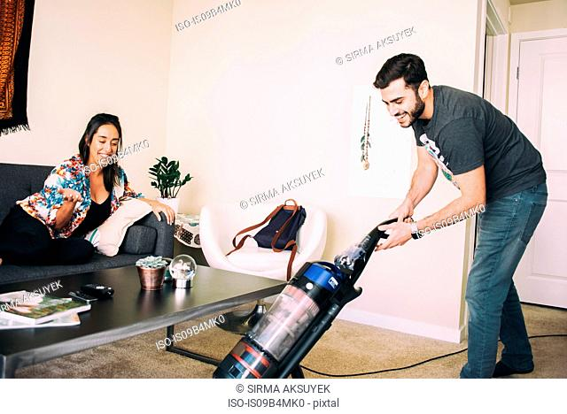 Woman supervising man vacuuming carpet