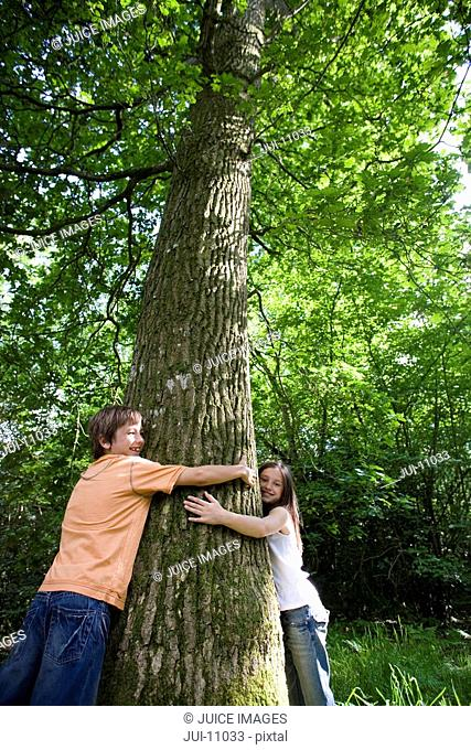 Brother and sister 7-11 embracing tree in forest, low angle view