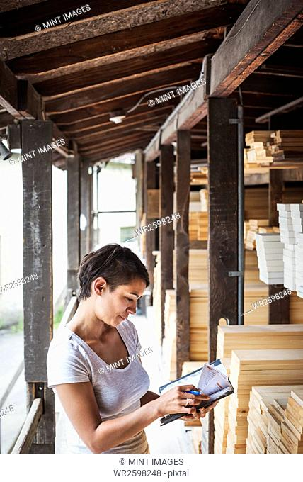 Woman standing in a lumber yard, holding a folder, checking notes