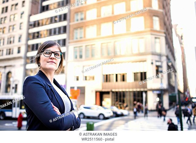 Confident businesswoman with arms crossed standing against buildings in city