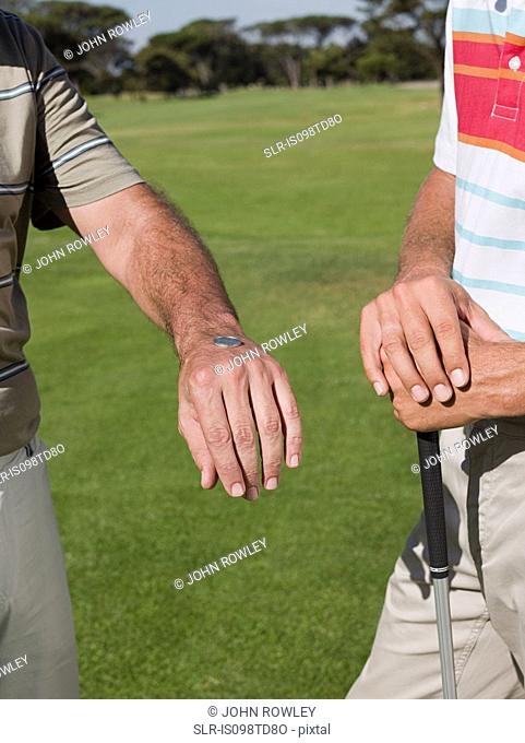Two mature men playing golf together, tossing a coin