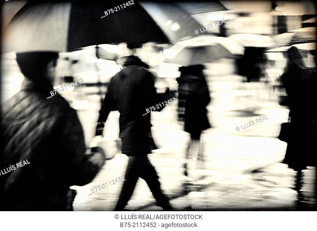 Blur unrecognizable peope with umbrellas on a rainy day in the city of London, England, UK, Europe