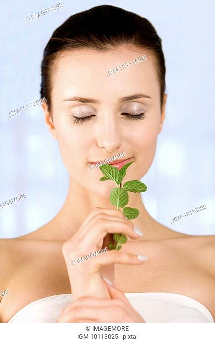Close-up of young woman smelling herbs and closing her eyes