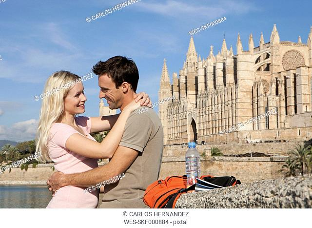 Spain, Mallorca, Palma, Couple embracing with St Maria Cathedral in background, smiling