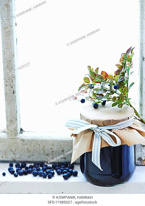 Blueberry jam with ginger in a glass jar on a window sill