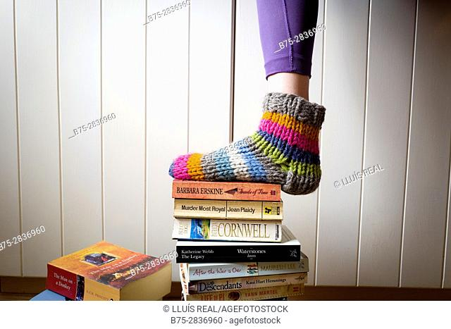 Feet of a woman with brightly colored socks standing on a pile of books. Buckden, Skipton, North Yorkshire, Yorkshire Dales, England, UK