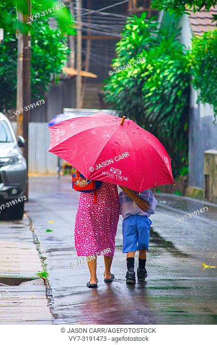 Indonesian mother and son walking in the rain with a pink umbrella. Jakarta is the biggest and main city in Indonesian islands