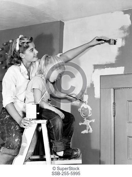 Mother and daughter painting wall at home