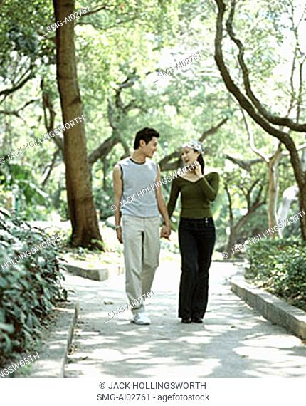 Young couple walking down path holding hands, nature in background