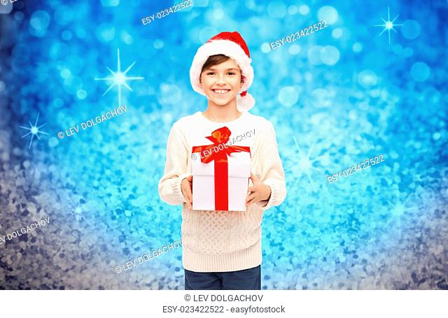 holidays, presents, christmas, childhood and people concept - smiling happy boy in santa hat with gift box over blue holidays lights background