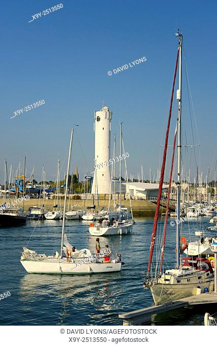 Pleasure boats yachts in Port du Crouesty marina in Baie de Quiberon, Brittany, France. Looking toward the lighthouse