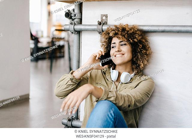 Young woman with headphones, working in coworking space, talking on the phone