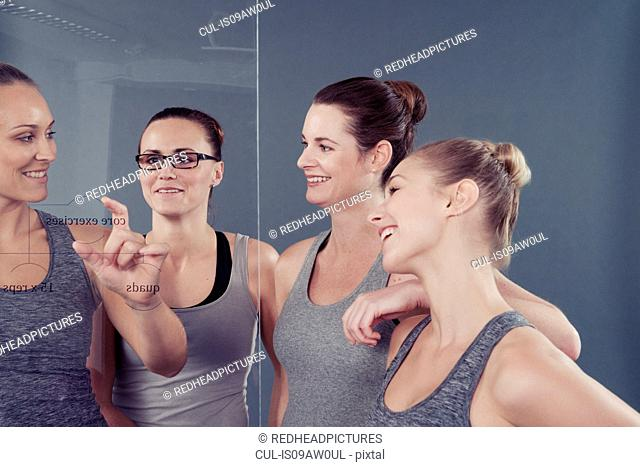 Young women studying chart on glass wall, grey background