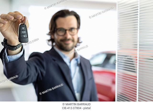 Portrait confident car salesman holding, showing car key in car dealership showroom