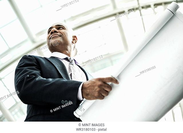 A black businessman holding plans for a new office space in a large glass covered walkway