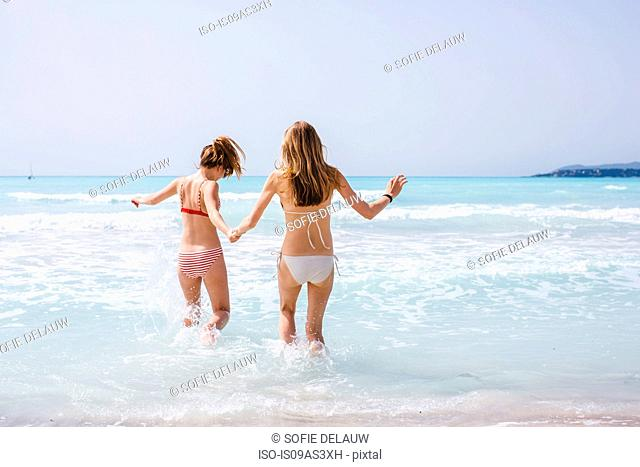 Rear view of two young female friends wearing bikinis running into sea