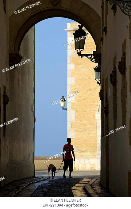 Young man with dog und the archway of Palau Maricel, Maricel de mar, Sitges, Catalonia, Spain, Europe