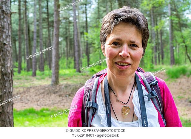 Esbeek, Netherlands. Mature adult woman strolling through a forest on a sunday afternoon