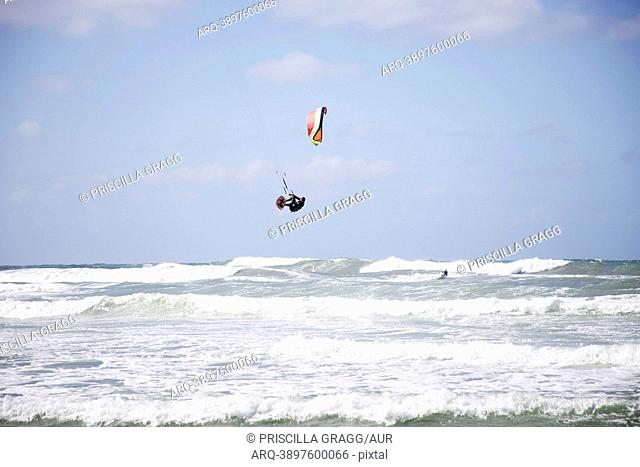 A male kitesurfer jumps and prepares to land while another male rides in the background