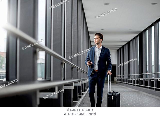 Young businessman in a passageway with cell phone, earbuds and rolling suitcase on the go