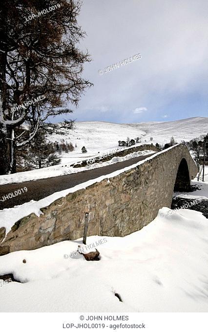 Scotland, Aberdeenshire, Glen Gairn, Snow covered historic bridge at Gairnshiel near Balmoral. This distinctive hump-backed bridge carries the A939 north to...