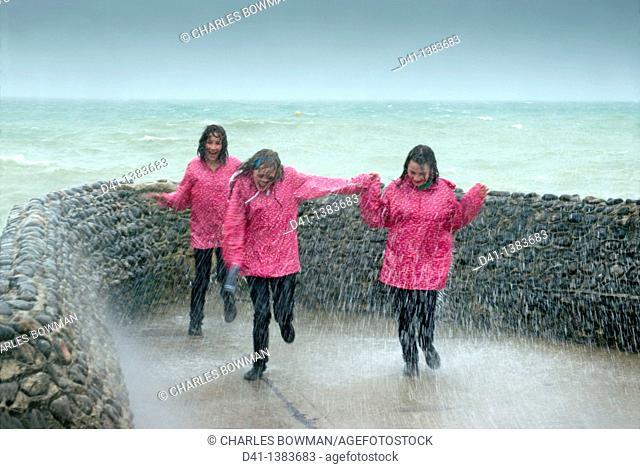 teenagers pink raincoats trio
