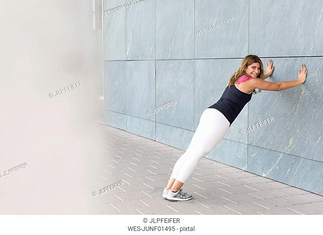 Smiling young woman leaning against wall doing stretching exercises