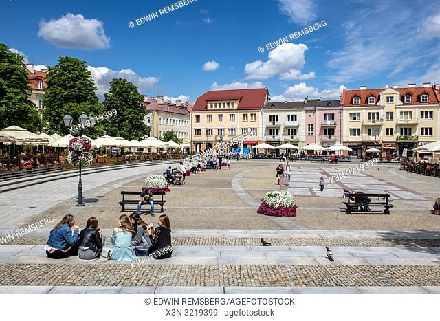 A group of women enjoy snacks while sitting in the Market square in Bialystok, Poland