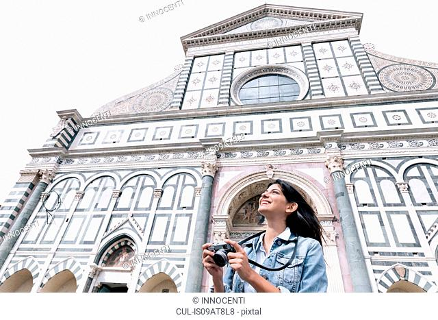 Low angle view of young woman using digital camera in front of church looking up, Piazza Santa Maria Novella, Florence, Tuscany, Italy