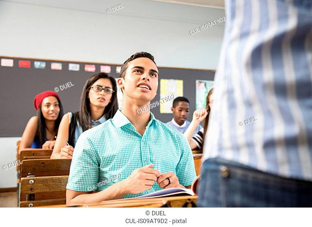 Male student talking to teacher in classroom