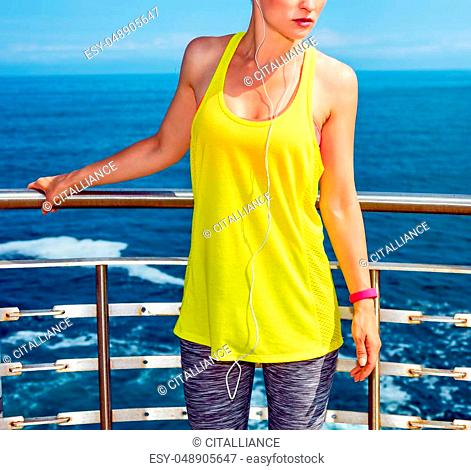 Look Good, Feel great! Relaxed young athlete in fitness outfit standing at the embankment