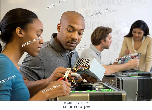 Black teacher and student working on equipment