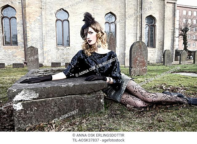 Lone female figure sitting by grave in churchyard