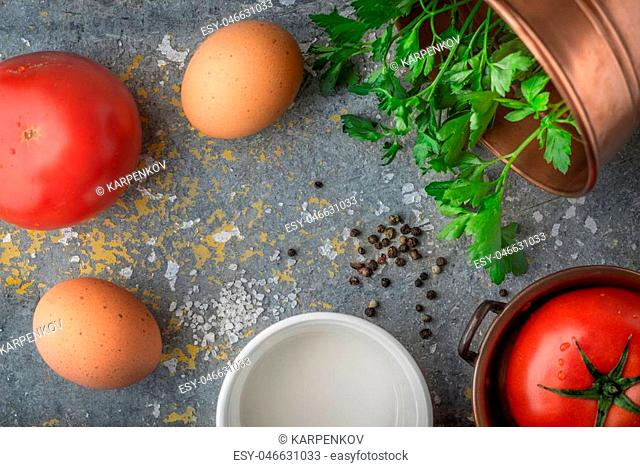 Ingredients for baked eggs with tomatoes on the stone table top view