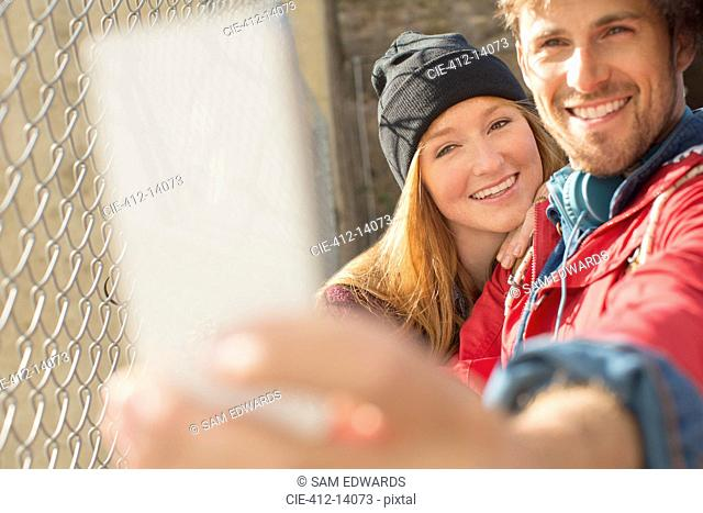 Couple taking self-portrait with camera phone next to chain link fence