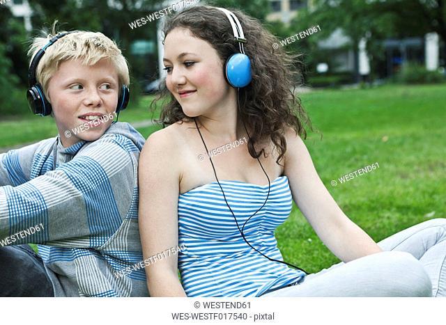 Germany, Berlin, Teenage couple with headphones listening music in park