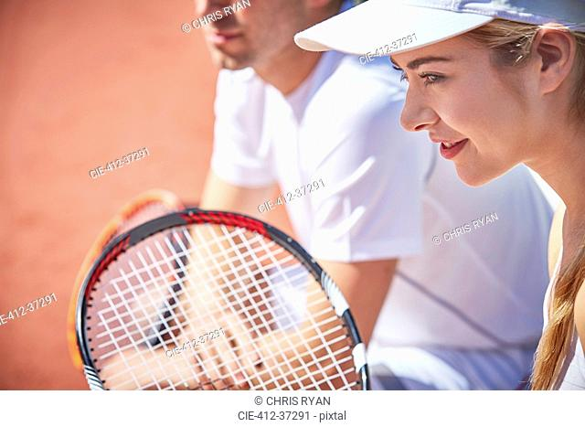 Smiling, confident young woman playing doubles tennis, ready with tennis racket