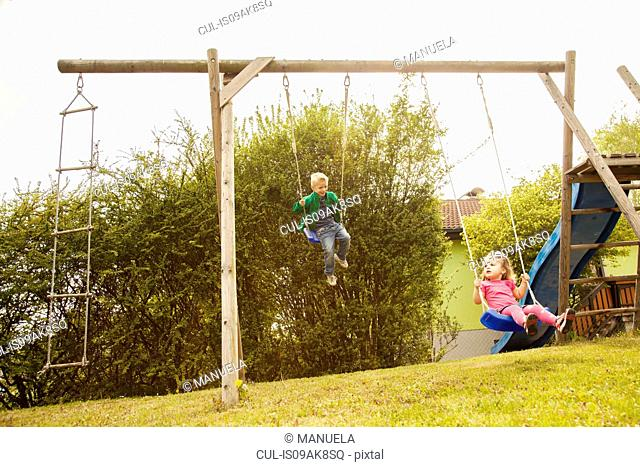 Brother and sister playing on swings in garden