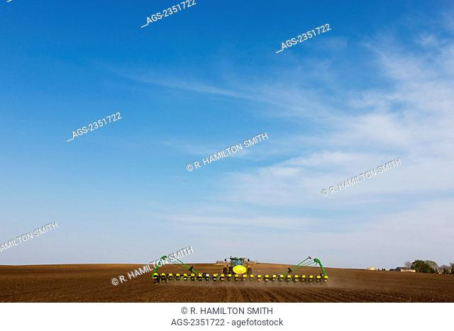 Agriculture - A John Deere tractor and 24-row planter planting corn in a vast conventionally tilled field / Minnesota, USA