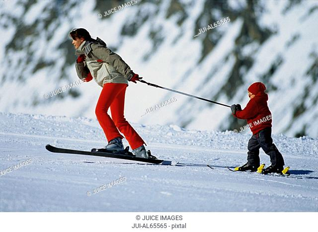 Mother pulling child on skis