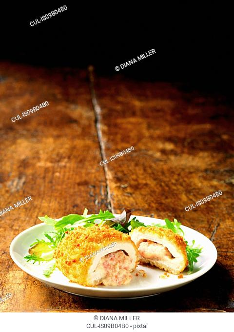 Chicken Kiev with cheese and ham filling on white plate with green salad leaves, vintage wooden table