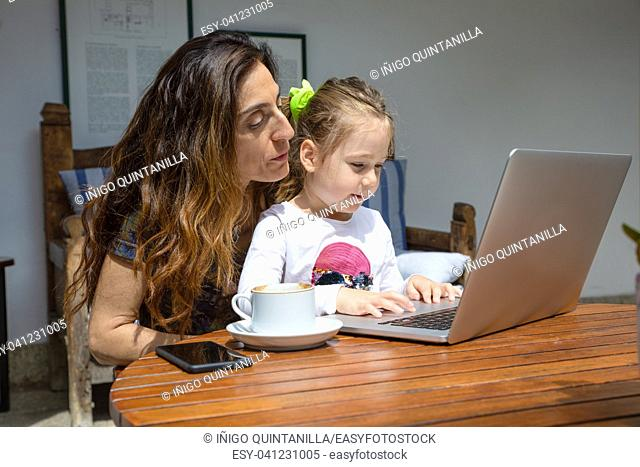 girl four years old sitting on mother legs, surfing internet in notebook computer together, with coffee cup and black mobile smart phone on brown wooden table