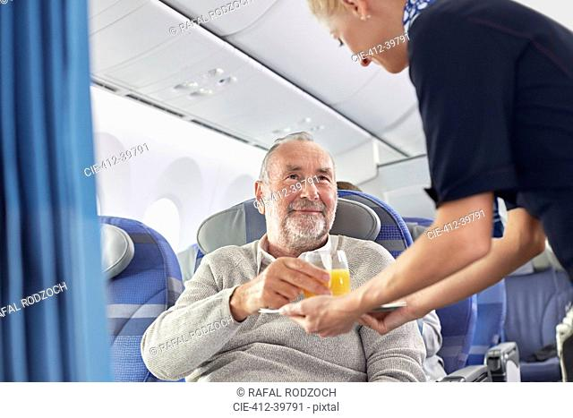 Flight attendant serving orange juice to man on airplane