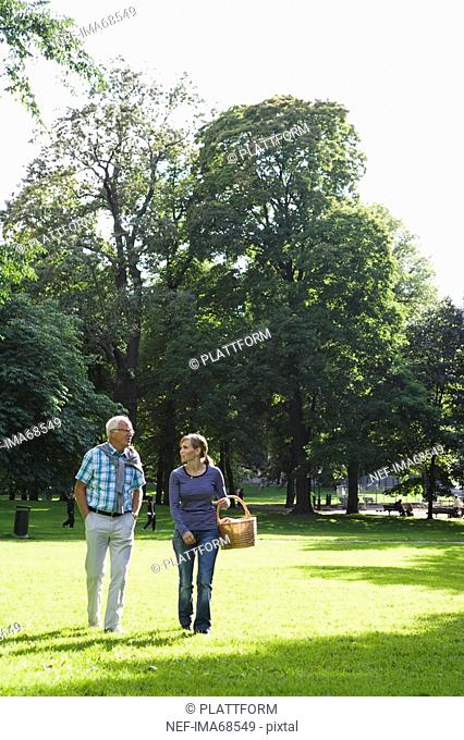 Woman and senior man walking in the park Sweden