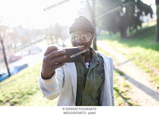 Young man standing in park, taking smartphone selfie