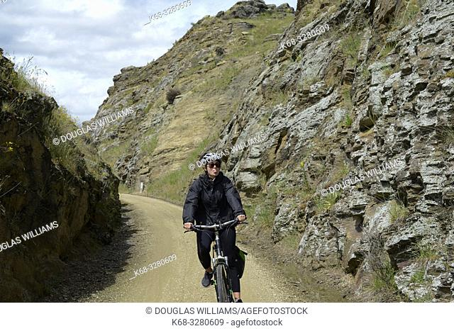 Woman bicycling on the Central Otago Rail Trail, South Island, New Zealand