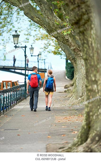 Mature man and young woman strolling along riverside, rear view, Annecy, Rhone-Alpes, France