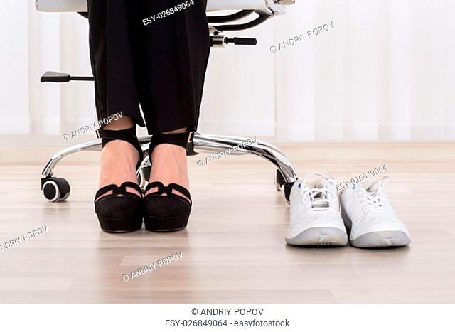 Pair Of A White Sport Shoes Besides Businesswoman's Foot Wearing High Heels